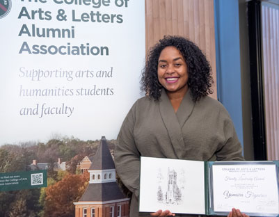 "woman with black hair holding award posing next to ""The College of Arts & Letters Alumni Association"" sign"