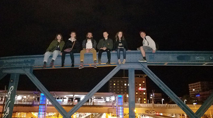 six people sitting on top of a bridge