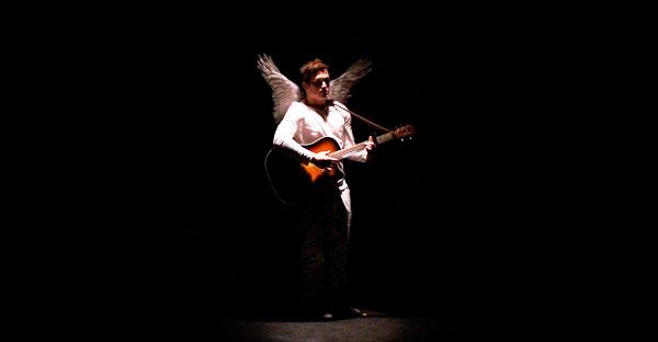 man dressed as angel playing guitar in spotlight