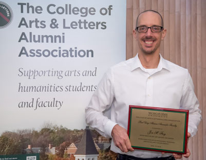 "man with glasses holds award posing next to ""The College of Arts & Letters Alumni Association"" sign"