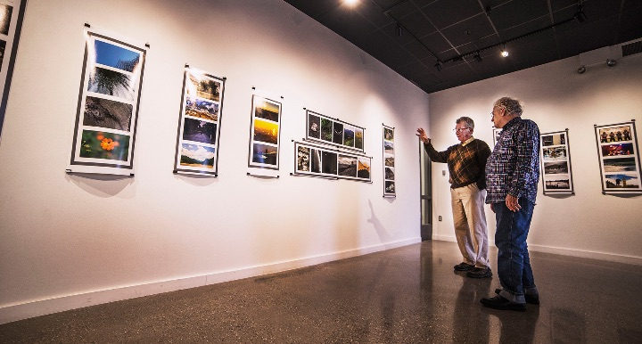 Mark Sullivan and Peter Glendinning looking at photographs in a gallery
