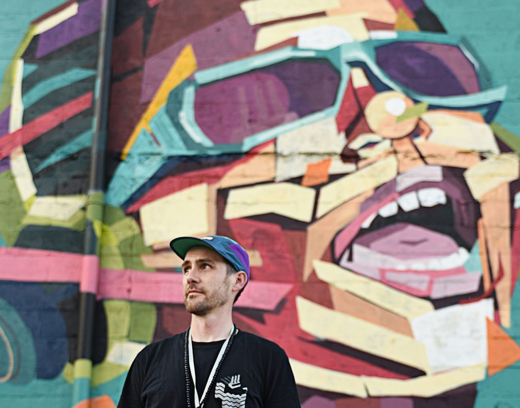 side of a building with a colorful mural with a man wearing a black tshirt and hat standing in front of it