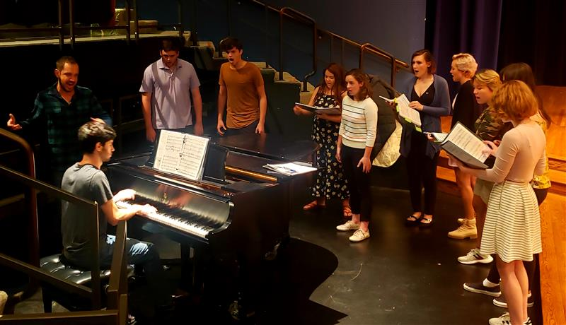 Group of 11 people standing around a piano singing