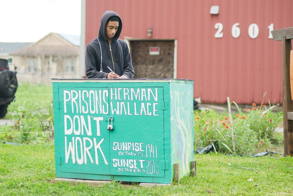"""man wearing a black hoodie is standing behind a teal wooden box that says """"prisons don't work' in white letters."""