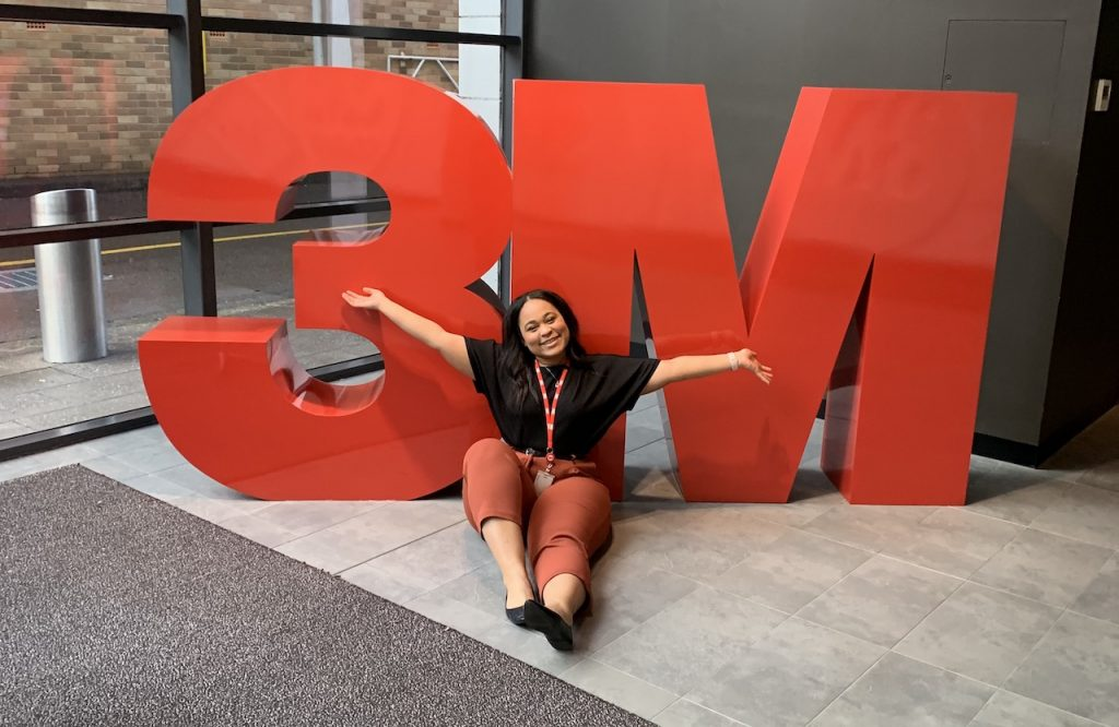 girl who's wearing a black shirt and red pants who is sitting with her arms spread open in front of a red sign that says 3M
