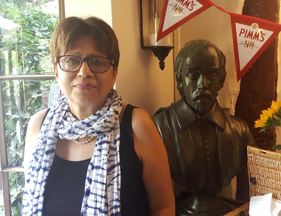 Woman with short hair and glasses standing next to a bust of a man