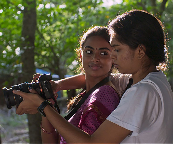 two women holding a camera taking photos