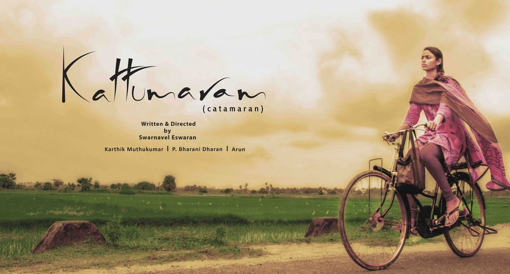 "Poster for the movie Kattumaran. The background is a green field and in the foreground on the right is a woman riding a bike. On the left in the foreground is the word ""Kattumaran"""