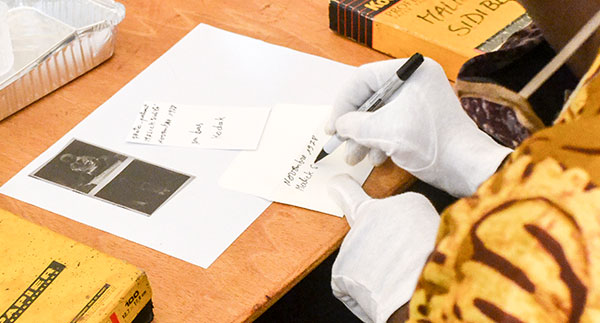 Person with white gloves carefully labeling and organizing photographs