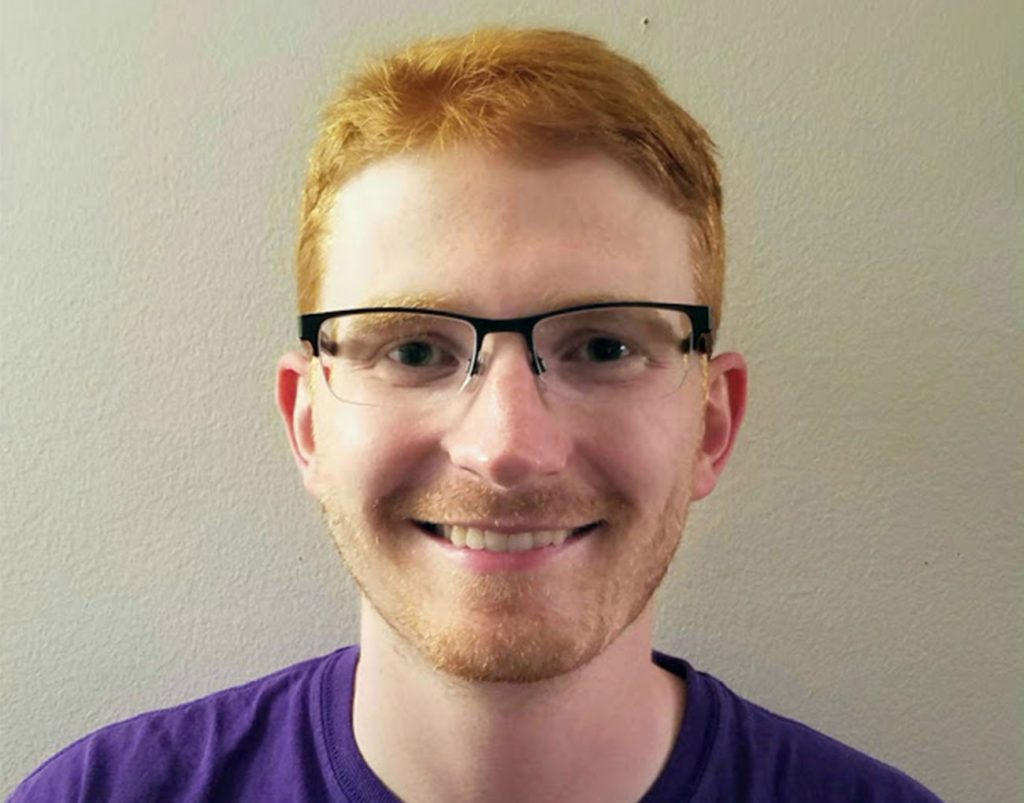 Man with red hair wearing black rimmed glasses and a purple shirt