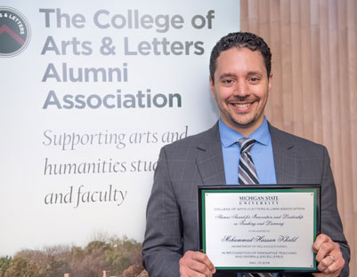 "man with brown hair holding award posing next to ""The College of Arts & Letters Alumni Association"" sign"