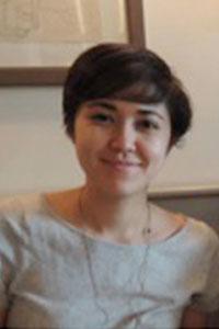 woman with short brown hair wearing a tan shirt smiling