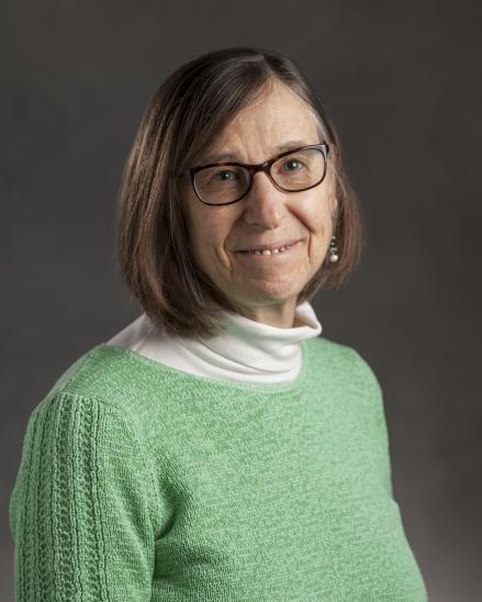 portrait of a woman with with short hair and glasses. she is wearing a sweater over a turtleneck