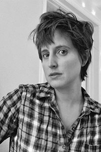 woman with short brown hair wearing a plaid button up shirt in greyscale