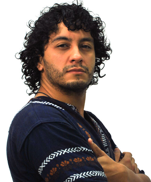 man with curly black hair is standing to the side. He is wearing a navy shirt with white and orange print