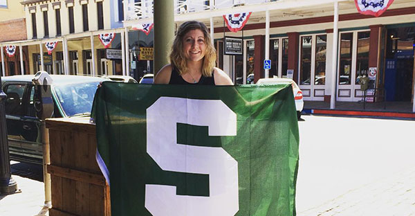 Blonde girl with curly hair holding a green Spartan flag