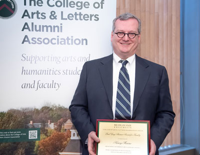 "man with glasses holding award posing next to ""The College of Arts & Letters Alumni Association"" sign"