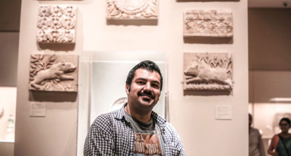 Man standing in front of an art exhibit. The man is wearing a graphic t-shirt and a blue and white checkered button up.