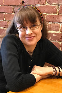 woman who's wearing glasses and a black shirt who's smiling slightly at the camera