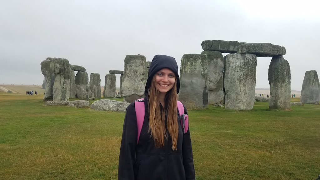 Woman in a black jacket with the hood on smiling at the camera in front of Stonehenge