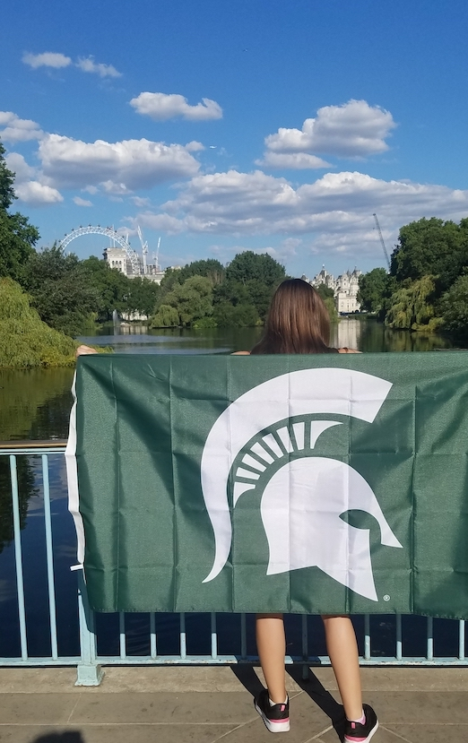 woman with long brown hair holding up a Michigan state flag facing water and blue sky