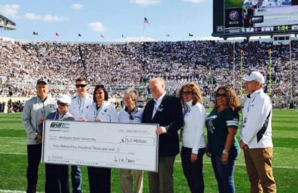 9 people standing on spartan stadium field, msu president accepting check