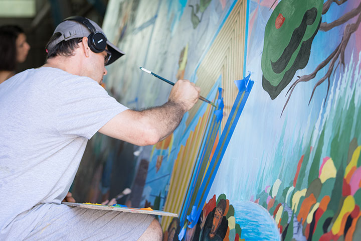 Man with headphones, a hat, and glasses painting a brightly colored mural.