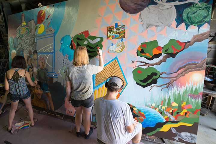 Two female students standing and painting a brightly colored mural while a man with a hat and headphones sits and paints beside them.
