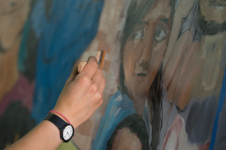 A hand with a black wristwatch painting a face onto a mural.