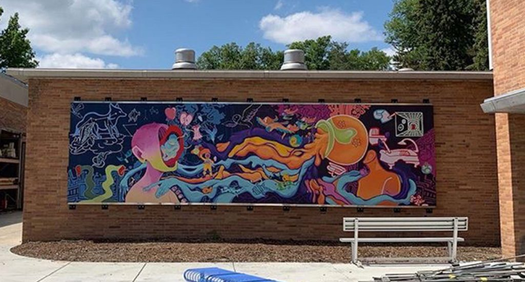 Colorful mural with two heads facing each other. It hangs against a brick building