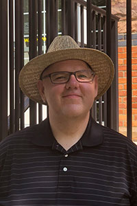 man with black striped polo wearing glasses and straw hat in front of a gate