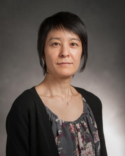 portrait of a woman with short, black hair. she is wearing a floral top and black cardigan