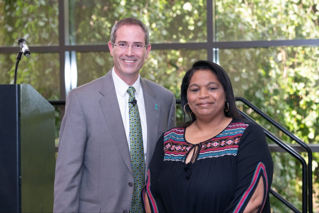 a man in a grey suit coat with a white shirt and green neck tie and a women with dark hair wearing a navy blue blouse with colors on the sleeves and neckline