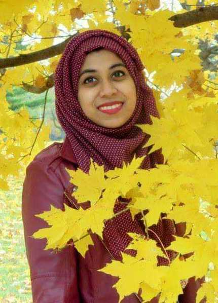 woman wearing all red standing in front of tree with yellow leaves