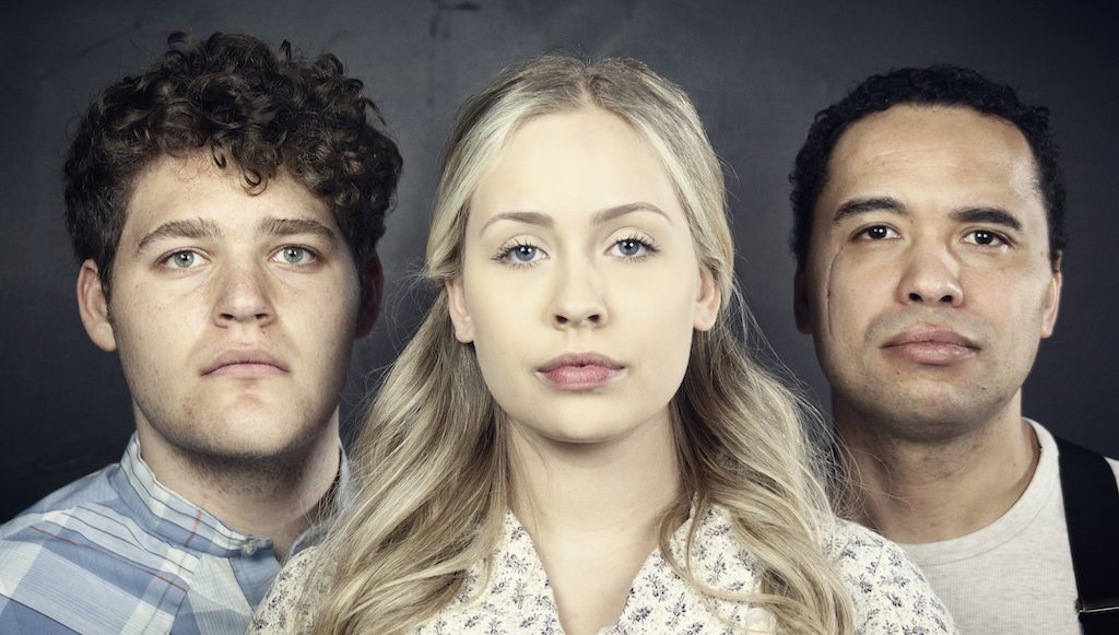 woman with blonde pigtails who has two men on each side of her, all are looking at the camera