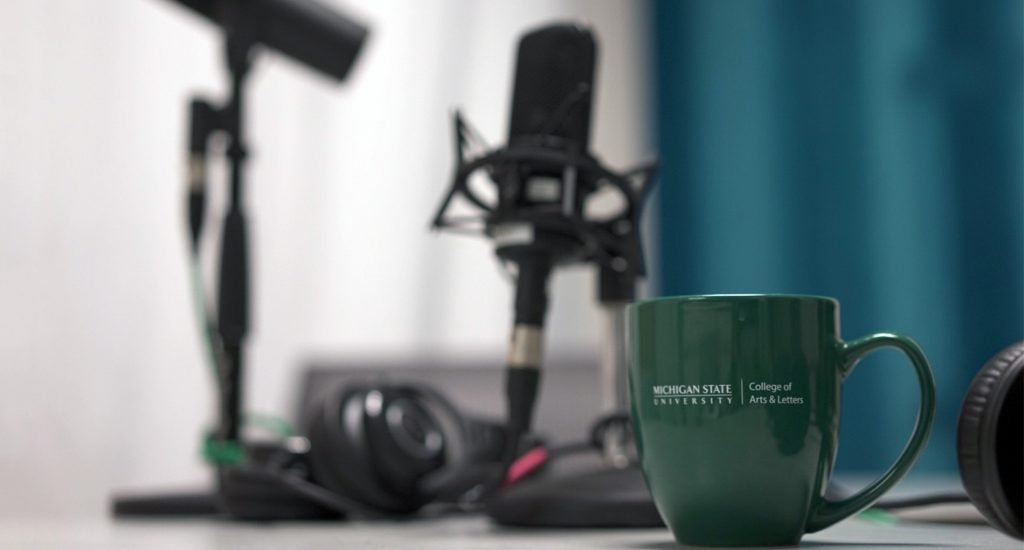Microphone with Michigan State University mug sitting on table