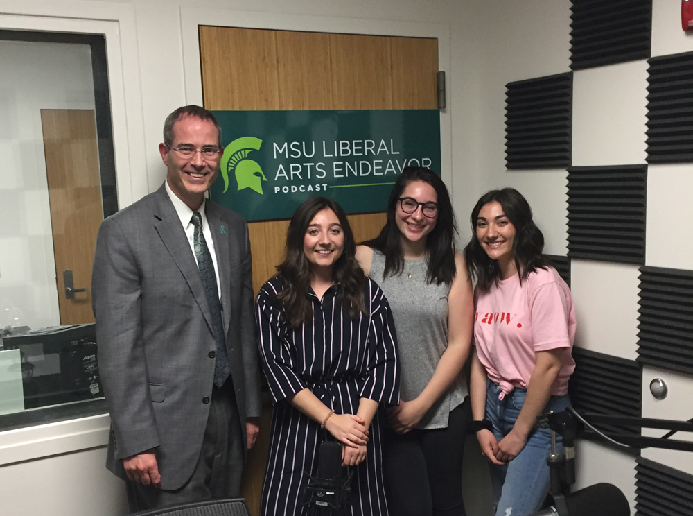 one man and three woman standing in a recording studio, there is a poster behind them that reads 'MSU liberal arts endeavor podcast;