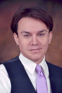 close up of man with brown hair and earrings wearing a dress shirt vest and tie