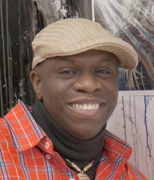 Headshot of a man wearing a tan hat, black turtleneck and red and blue plaid button up