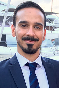 close up of man with mustache and short beard wearing a suit at a boat dock