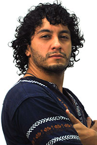 man with curly black hair who's wearing a sweater with the pattern around the arm