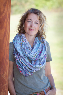headshot of a blonde woman that is wearing a gray t-shirt and blue patterned scarf, her hair is curly