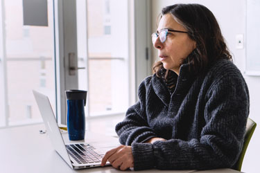 Woman sitting next to bright windows in front of laptop with coffee cup.