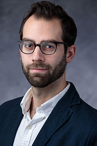 man with short dark hair and a beard who's wearing glasses, a white button-up shirt and a dark suit jacket