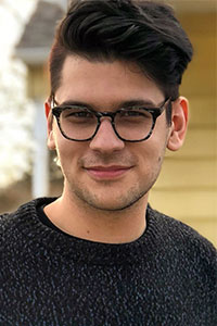close up of man with brown hair and grey sweater wearing glasses in front of a house
