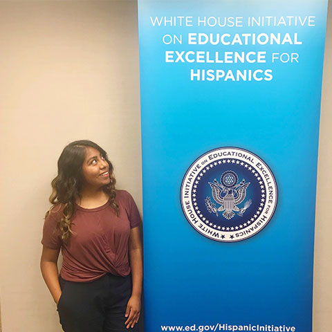 girl in red shirt standing next to blue white house education sign