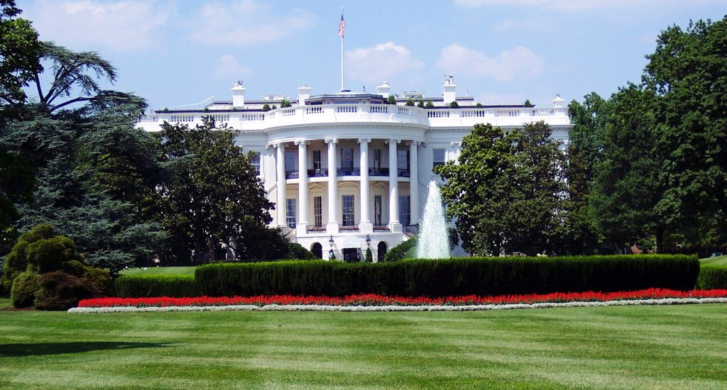 white house with columns on manicured green lawn with red flowers and trees