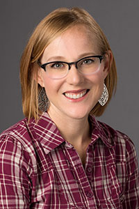 woman with short red hair who's wearing glasses and a flannel shirt who's smiling