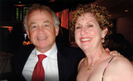 a man in a black suit with a white button down shirt and red tie and a lady with curly short hair in a dress