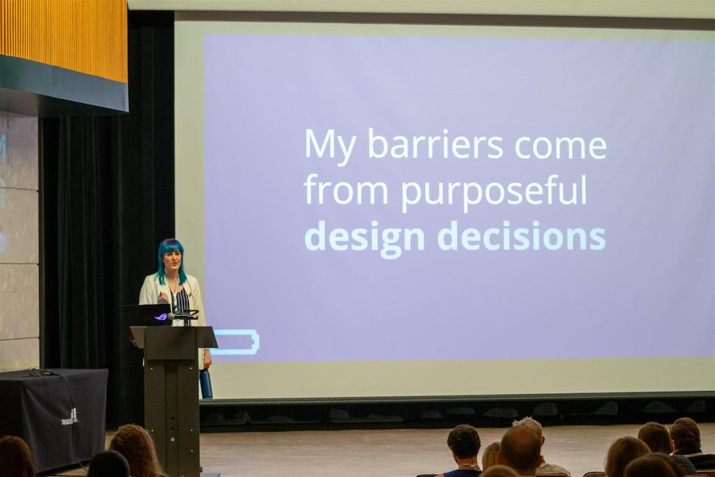 women standing at podium with her presentation that says 'my barriers come from purposeful design decisions